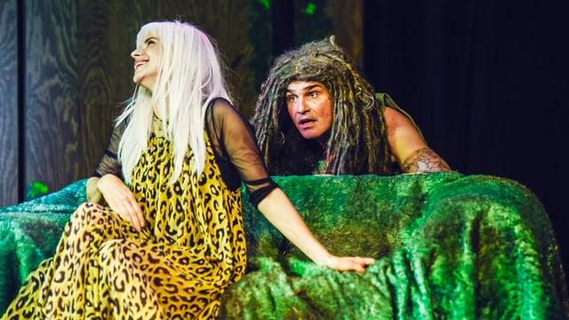 Eine blonde Hippolita sitzt auf einem grünen Sofa, über die Lehne schaut ein Oberon mit Dreadlocks.
