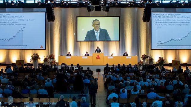 Versammlung in einem grossen Saal mit einem Bildschirm. Darauf Verwaltungsratspräsiden der Sika, Paul Hälg.
