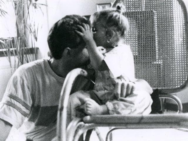 Ein kleines Mädchen auf einem Stuhl greift nach seinem Vater.