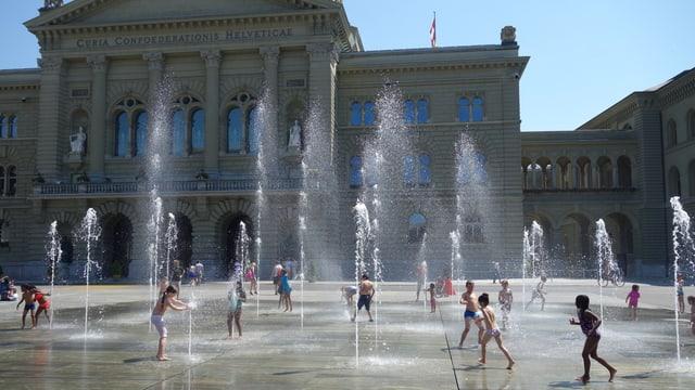 Kinder suchen Abkühlung bei den Wasserfontänen auf dem Bundesplatz.