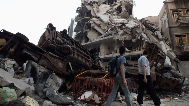 Männer laufen an zerstörten Gebäuden vorbei