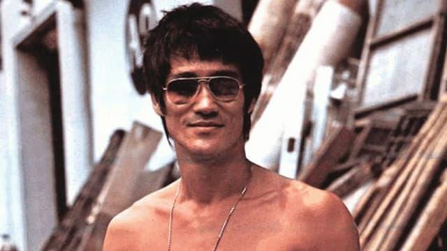 Nahaufnahme von Bruce Lee mit Sonnenbrille und nacktem Oberkörper.