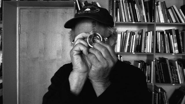Ein Mann mit einem Vergrösserungsglas vor dem linken Auge.