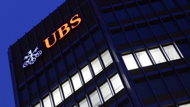 Leuchtendes UBS-Logo an einem Gebäude.