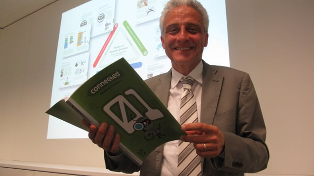 Lachender Mann im Anzug mit Buch in der Hand  vor Projektionswand