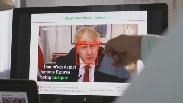 Mann zeigt am Bildschirm auf ein Deep-Fake-Video von Boris Johnson.