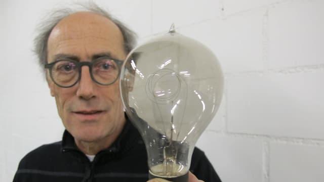 Denkmalpfleger Peter Baumgartner mit einer Kohlefaden-Glühbirne.