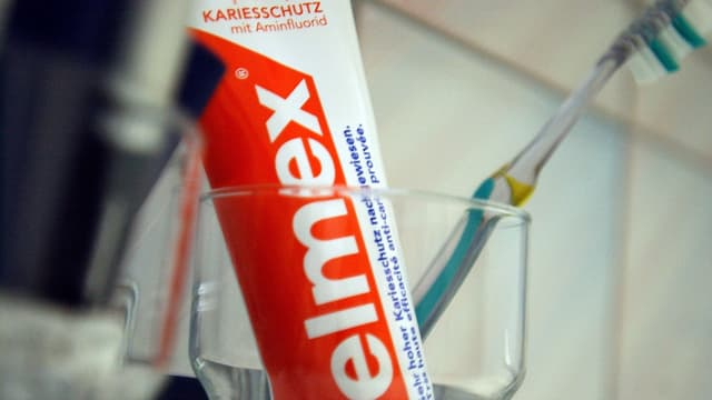 Elmex-Zahnpasta in einem Glas.