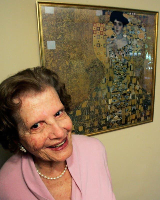 Maria Altmann posiert vor der goldenen Adele von Gustav Klimt.