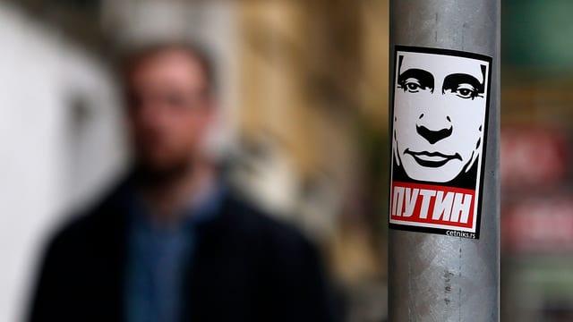 Eine Stange mit einem Putin-Sticker darauf, ein Mann geht vorbei.
