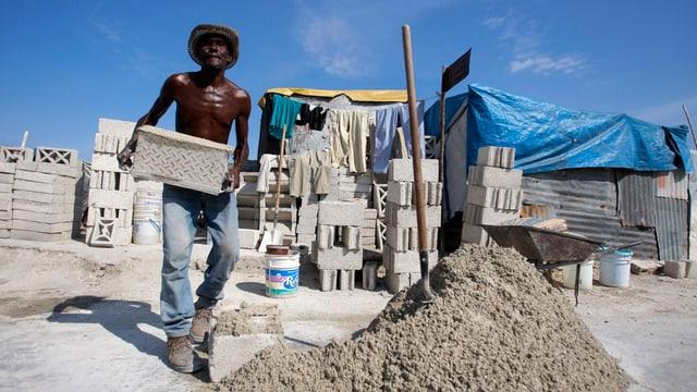Ein Haitianer schleppt einen Ziegelstein