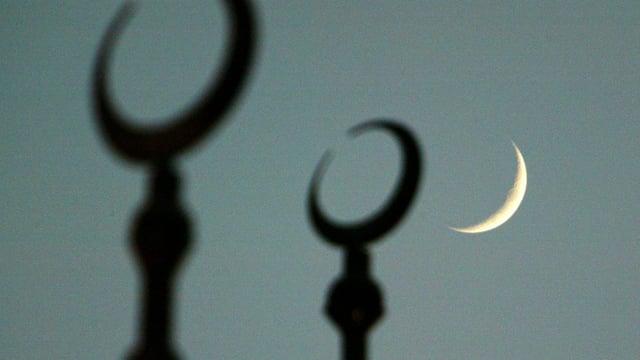 Mondsichel neben der Spitze einer Moschee.