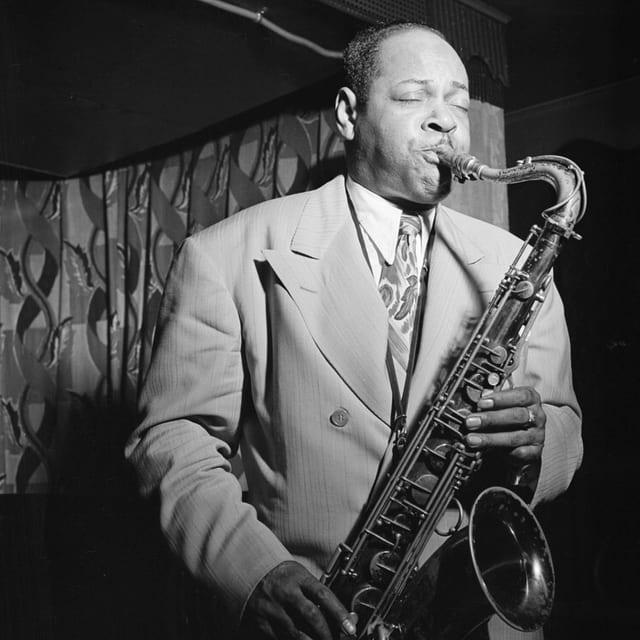 Ein Mann in Anzug und Krawatte auf einer Bühne, Saxophon spielend.
