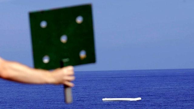 Von einem Kriegsschiff zeigt ein Mann mit einem Schild auf ein leeres Gummiboot vor der Küste Libyens, auf dem zuvor Migranten waren.