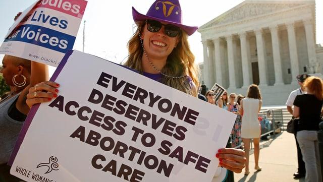"""Eine Frau mit einem Plakat, auf dem """"Everyone Deserves Access to Safe Abortion Care"""""""