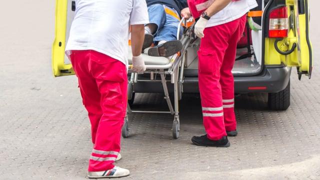 Sanitäter stossen Mann auf Trage in Ambulanz