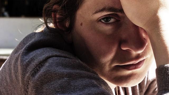 Erschöpfte Frau blickt traurig und müde in die Kamera.