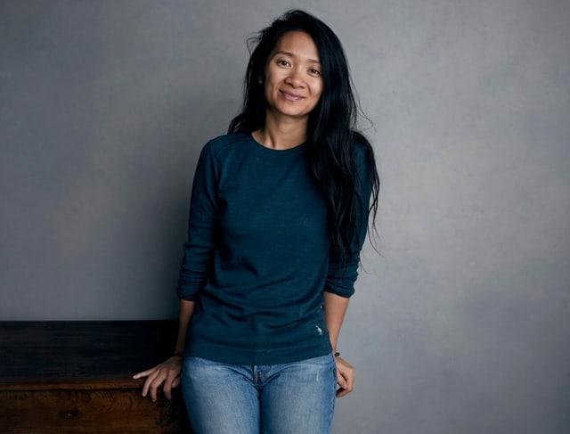Zhao lehnt an einer grauen Wand und lächelt in die Kamera.
