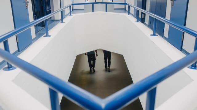 Blick durch eine Öffnung im Boden auf ein tieferliegendes Stockwerk. Dort gehen zwei Personen nebeneinander.