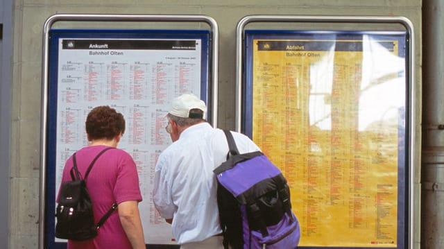 Ein Mann und eine Frau stehen vor einem Fahrplan der SBB.