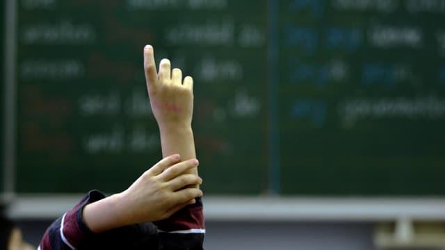 Ein Kind reckt die rechte Hand in die Höhe und meldet sich im Unterricht zu Wort. Im Hintergrund eine Wandtafel.