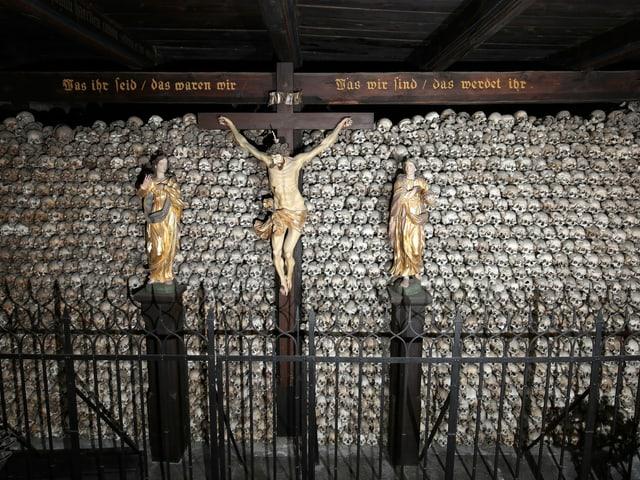 Figur von Jesus am Kreuz, dahinter Wand mit Totenschädeln