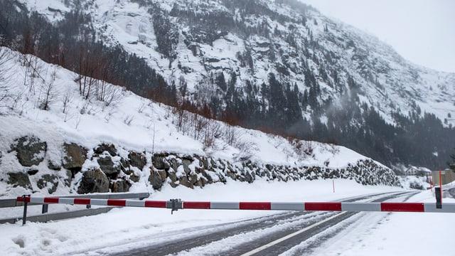 Eine verschneite Strasse mit einer Barriere.
