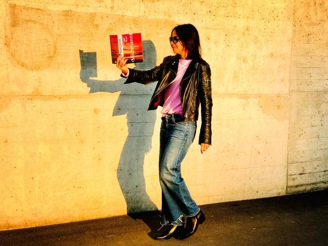 Annette König liest im Gehen und hält dabei den Roman «Milchmann» von Anna Burns in der Hand