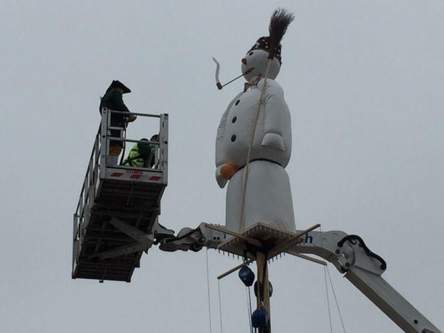 Sechseläutenbögg, daneben Männer auf einer Bauplattform