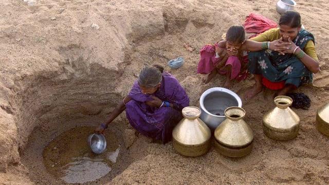 Drei Frauen hocken im ausgetrockneten Flussbett und schöpfen Wasser aus einem kleinen Loch.
