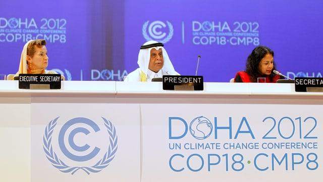 Der Vertreter von Katar sitzt mit zwei UNO-Vertreterinnen am Konferenztisch.