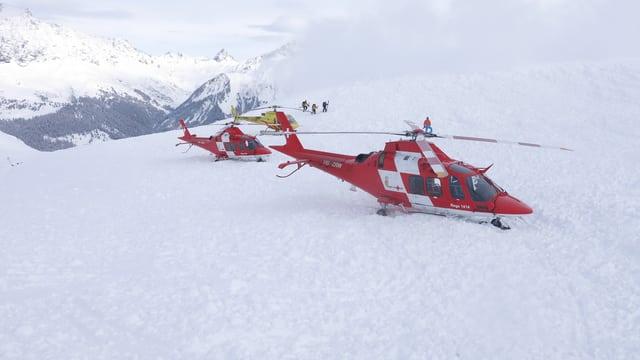 Rote Rega-Helikopter stehen auf dem Lawinenkegel.