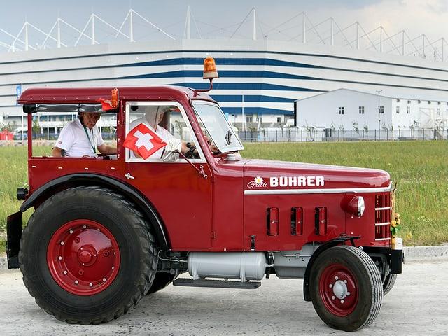 Josef Wyer, Beat Studer und Werner Zimmermann posieren mit einem Traktor (Baujahr: 1964) vor dem Stadion in Kaliningrad.