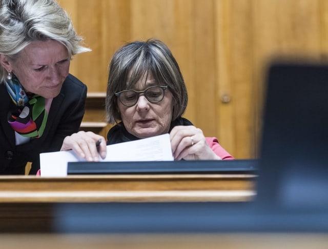 Zwei Frauen beugen sich über ein Akte.