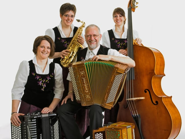 Drei Musikantinnen und ein Musikant mit ihren Instrumenten auf einem Gruppenbild.