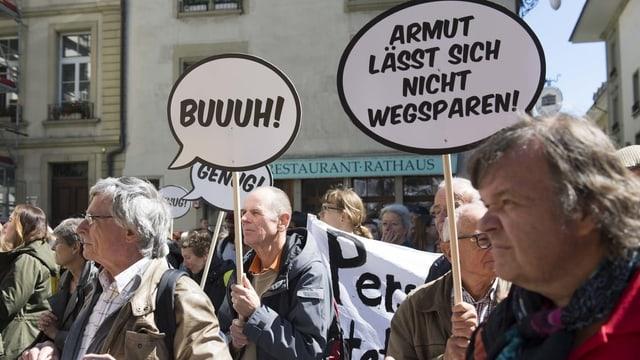 Demonstranten mit Plakaten. Dort steht «Buuuh» und «Armut lässt sich nicht wegsparen»