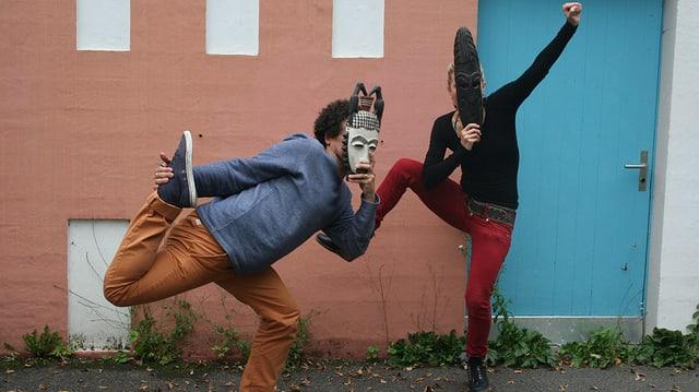 John und Rosanna mit afrikanischen Masken und Körperverrenkungen