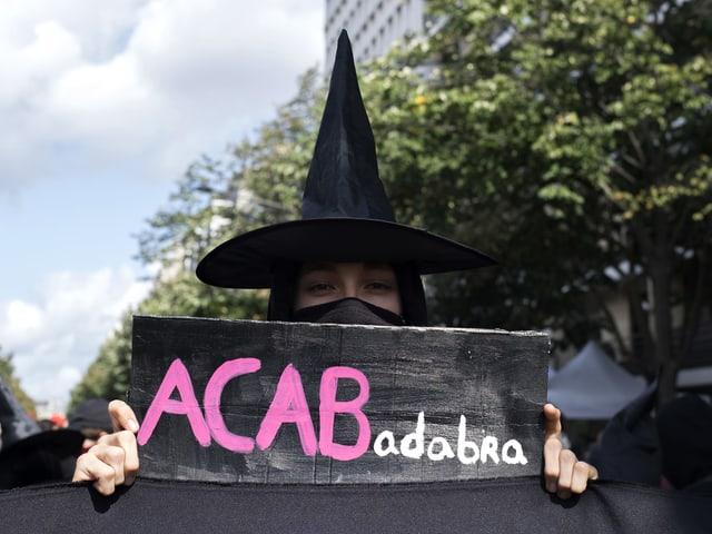 Eine Demonstrantin geht auf die Strasse als Hexe verkleidet.