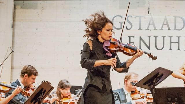 Eine Geigerin spielt ihr Instrument. Ihre Haare fliegen durch die Luft. Sie zeigt vollen Einsatz.