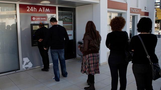 Menschen stehen Schlange von einem zyprischen Bankomaten.