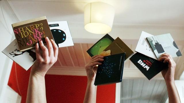 Drei Hände halten je verschiedene CDs in die Luft.