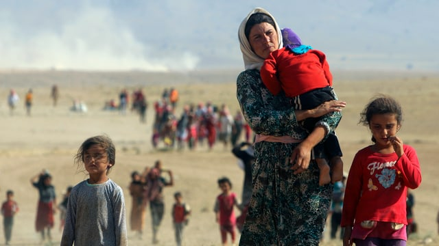 Frauen und Kinder marschieren durch die irakische Wüste.