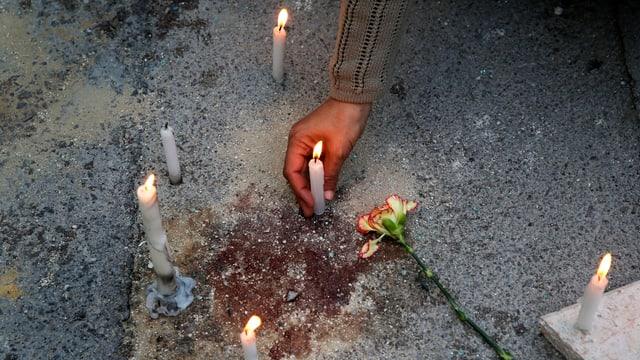 Eine männliche Hand zündet Kerzen rund um einen Blutfleck an.