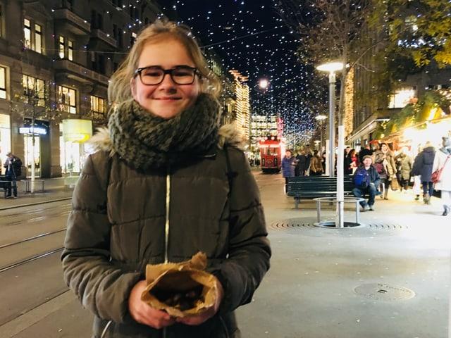 Rahel steht an der Bahnhofsstrasse in Zürich und hält eine Marroni-Tüte in den Händen.