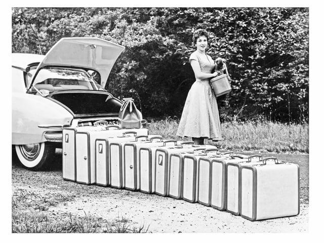 Gina Lollobrigida mit 13 Koffern vor einer DS.