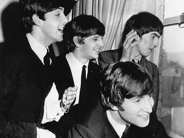 Die Beatles 1964 an einem Fenster.