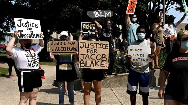 """Menschen halten Plakate hoch mit der Aufschrift: """"Justice for Jacob Blake"""" und """"Black Lives Matter""""."""