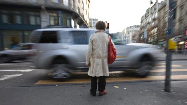 Person von hinten, die am Fussgängerstreifen wartet, während ein Auto vorbeifährt