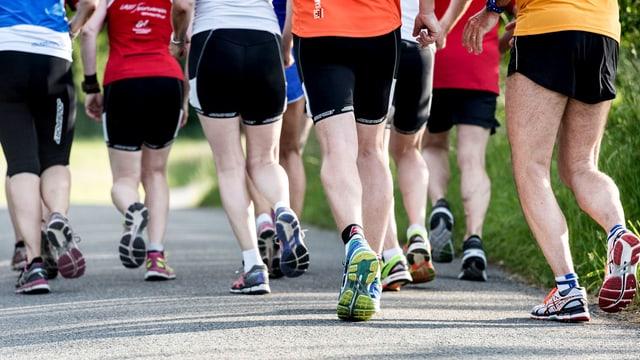 Beine von Joggern und Joggerinnen, die dicht beieinander laufen.