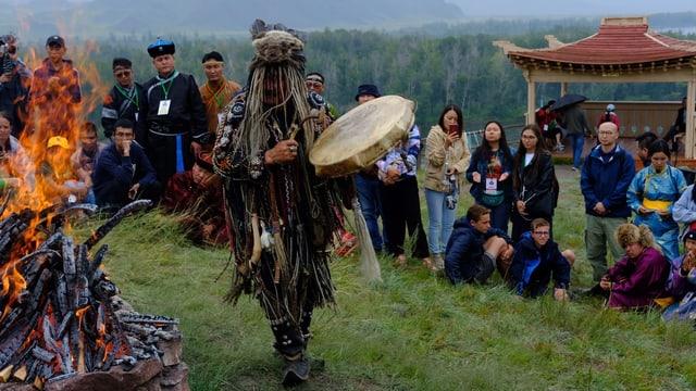 Ein Mann mit einem Bärenfell auf dem Kopf tanzt um ein Lagerfeuer und schlägt auf eine Trommel.
